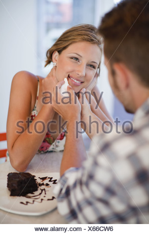 Man cleaning chocolate off woman's face - Stock Photo