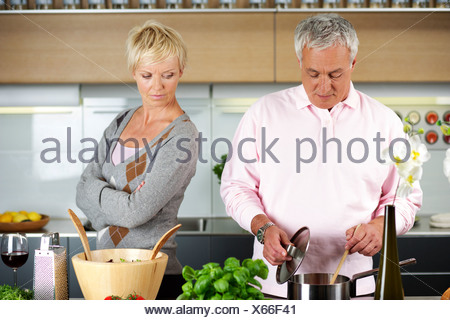 Blond woman turned away from a man who is cooking - Stock Photo