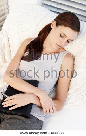 Businesswoman sleeping on sofa - Stock Photo