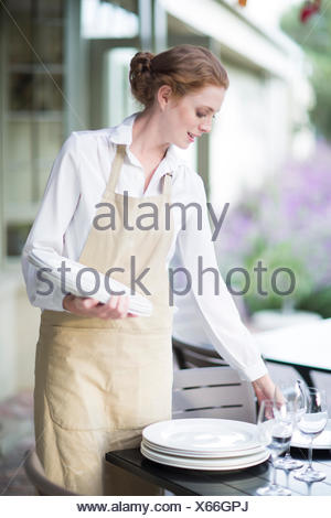 Waitress organizing plates on table in patio restaurant - Stock Photo