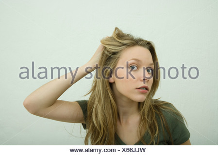 Teen girl with hand in hair - Stock Photo