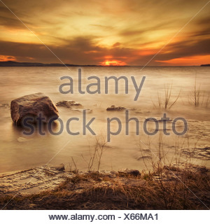 Setting sun over a frozen lake - Stock Photo