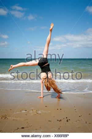 A woman doing a cartwheel on a beach - Stock Photo