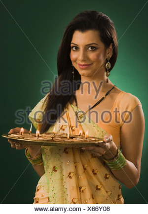 Woman holding a traditional Diwali thali and smiling - Stock Photo