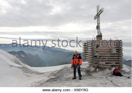 Mountaineer, successful ascent, summit cross on the top of Mt Grossvenediger, 3662 m, near Neukirchen am Grossvenediger - Stock Photo