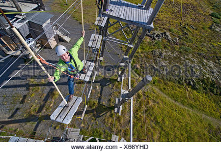 Mature man walking on wooden planks on high rope course - Stock Photo