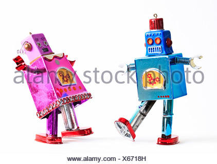 Toy tin robots dancing as a couple - Stock Photo