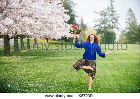 Portrait of young woman practicing yoga whilst holding bunch of flowers in park - Stock Photo