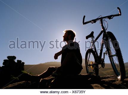 A man sitting on a rock next to a mountain bike - Stock Photo