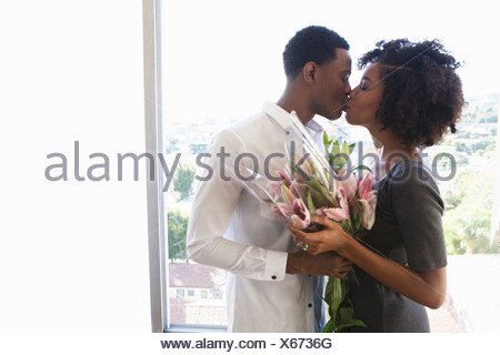 Young couple kissing, woman holding bouquet - Stock Photo