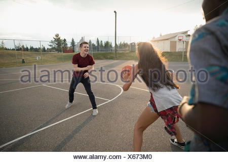 Teenage friends playing basketball on outdoor basketball court - Stock Photo