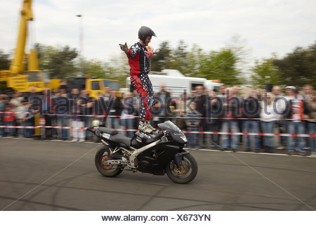 Motorcycle stuntman Mike Auffenberg standing on the seat of his motorcycle, Koblenz, Rhineland-Palatinate, Germany, Europe - Stock Photo