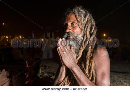 Shiva sadhu, holy man, sitting and praying at night at the Sangam, the confluence of the rivers Ganges, Yamuna and Saraswati - Stock Photo
