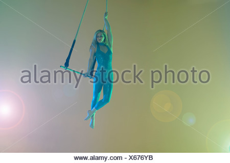 Trapeze artist holding trapeze - Stock Photo