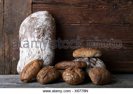 Loaf of Bread and rolls on a rustic wooden surface - Stock Photo
