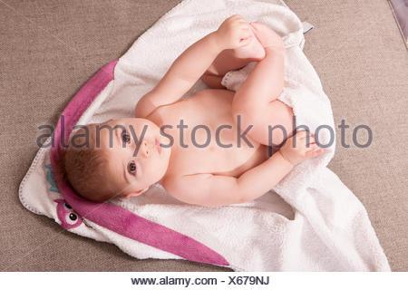 Baby girl lying on bath towel - Stock Photo