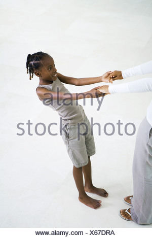 Little girl holding mother's hands, leaning back, cropped view - Stock Photo