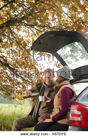 Senior couple having flask of coffee from car boot, Norfolk, UK - Stock Photo