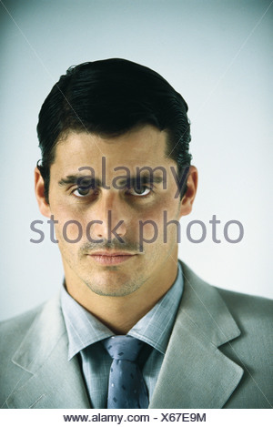 Businessman looking confidently at camera, portrait - Stock Photo