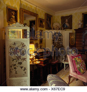 Painted antique folding screen in drawing room in Jacobean rectory with antique furniture and a lighted lamp - Stock Photo