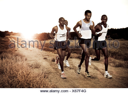 Kenyan marathon runners at sunset - Stock Photo