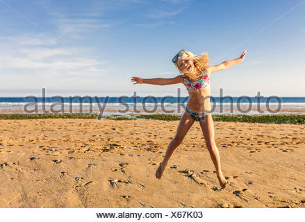 Spain, Colunga, little girl with diving mask jumping in the air on the beach - Stock Photo