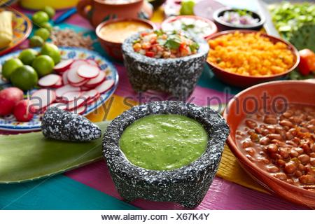 Green sauce with tomato and chili pepper in a mexican food table. - Stock Photo