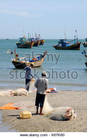 Fishermen and fishing boats in the fishing port of Mui Ne on the South China Sea, South Vietnam, Southeast Asia - Stock Photo