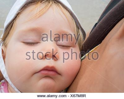 close up face of baby with white hat sleeping in rucksack mom arms. - Stock Photo
