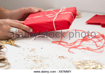 Cropped Image Of Hand Holding Gift Box On Table - Stock Photo
