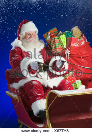 Santa Claus in sleigh with bag of toys - Stock Photo