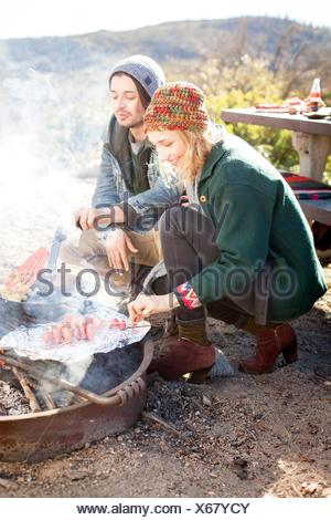 Young couple cooking food outdoors, in rural setting - Stock Photo