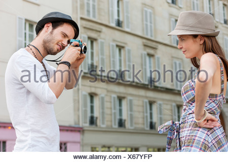 Man taking a picture of a woman standing with her hand on her hip, Paris, Ile-de-France, France - Stock Photo