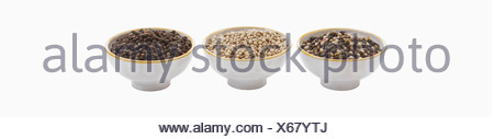Variety of peppercorns in bowl against white background, close up - Stock Photo