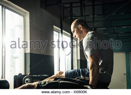 Mid adult man doing push up training in gymnasium - Stock Photo