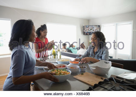 African American mother and teenage daughters cooking in kitchen - Stock Photo