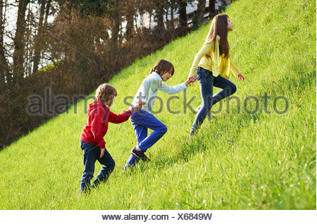 Sister and younger brothers climbing up grassy field - Stock Photo