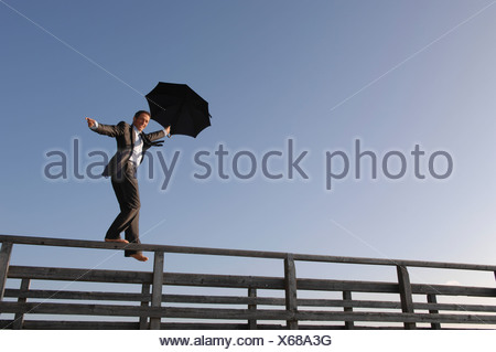 Germany, Bavaria, Ammersee, Mature businessman holding umbrella and balancing on railings of jetty - Stock Photo
