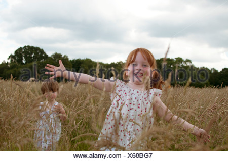 Two little girls playing in a field, one with arms outstretched - Stock Photo