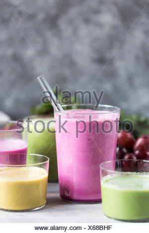 Several glasses of Multi-Colored Beet Smoothies are photographed from the front view. - Stock Photo