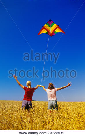 two girls in a spring wheat field flying a kite near Winnipeg, Manitoba, Canada - Stock Photo