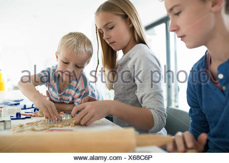 Brothers and sister baking with cookie cutters - Stock Photo