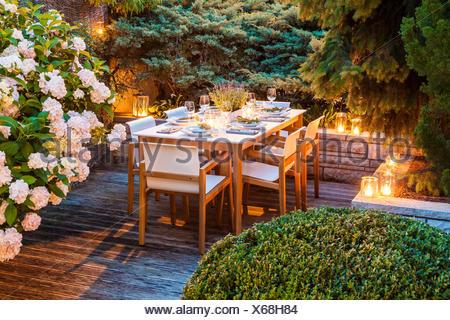 Deutschland, Garten, Terrasse, Holzdeck, Gartenmöbel, moderne Sitzgruppe, gedeckter Tisch, festlich, Tischdeko Lavendel, Lichter, Buchsbaum (Buxus sem - Stock Photo