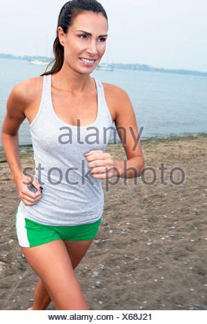 Woman Jogging On A Beach - Stock Photo