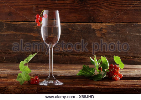 A glass of red currant schnapps with red currants (Ribes rubrum) on wooden background - Stock Photo