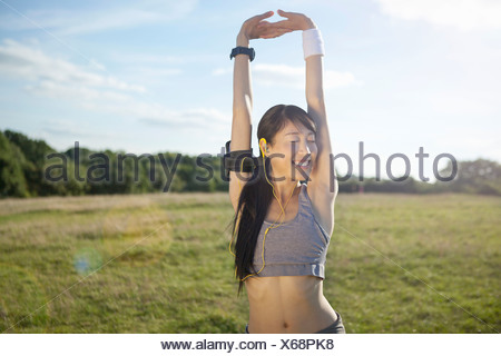 Young female runner stretching arms and warming up - Stock Photo