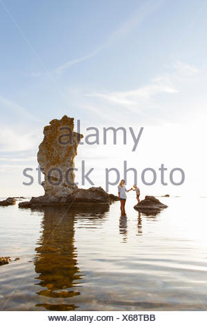 Sweden, Gotland, Faro, Mother with son (2-3) standing among rocks on Baltic Sea - Stock Photo