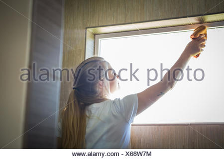 Young woman cleaning window with green cleaning products - Stock Photo