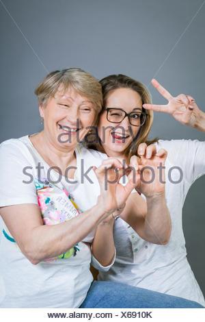 lachende junge enkeltochter mit glücklicher großmutter portrait vor grauem hintergrund - Stock Photo