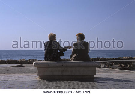 Spain, Altea, women, two, bank, sit, discuss back view, sea, Europe, vacation, senior citizens, older, entertainment, maintained, relaxing, view, enjoy - Stock Photo